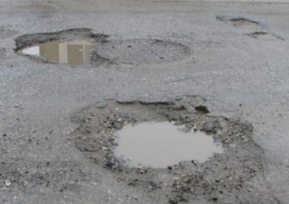 Surface treated road with two potholes